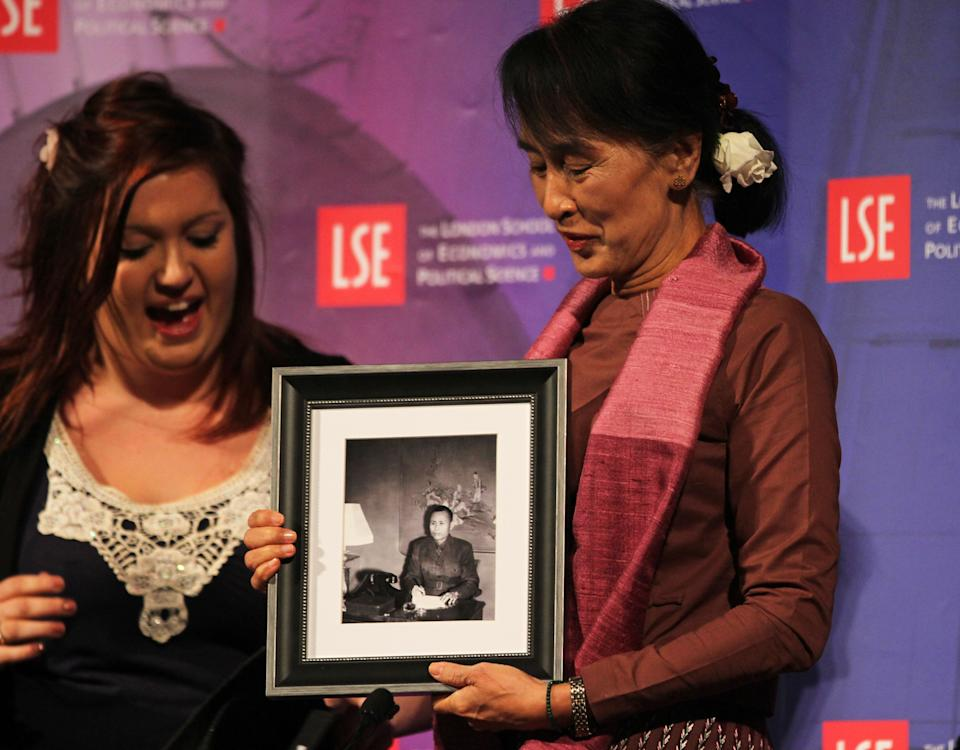Myanmar political leader Aung San Suu Kyi is given a picture of her father in London for her birthday, after taking part in a round table at The London School of Economics and Political Science during the first public event of her UK  visit in London Tuesday June, 19, 2012. (AP Photo/Elizabeth Dalziel)