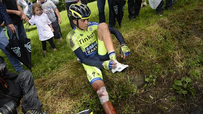 Spanish rider Alberto Contador sits on a verge after his fall on July 14, 2015 during the tenth stage of the Tour de France, between Mulhouse and La Planche des Belles Filles