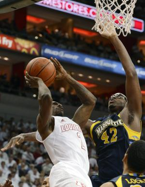 Louisville's Russ Smith, left, attempts a shot over the defense of Marquette's Chris Otule during the second half of their NCAA college basketball game on Sunday, Feb. 3, 2013, in Louisville, Ky. Louisville defeated Marquette 70-51. (AP Photo/Timothy D. Easley)