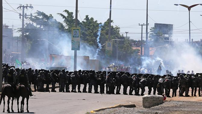 Riot police take position and fire tear gas at protesters gathering near Castelao stadium in Fortaleza, Brazil, Wednesday, June 19, 2013. Protesters cut off the main access road to the stadium where Brazil will play Mexico in the Confederations Cup soccer tournament later Wednesday. Beginning as protests against bus fare hikes, the demonstrations have quickly ballooned to include broad middle-class outrage over the failure of governments to provide basic services and ensure public safety. (AP Photo/Andre Penner)