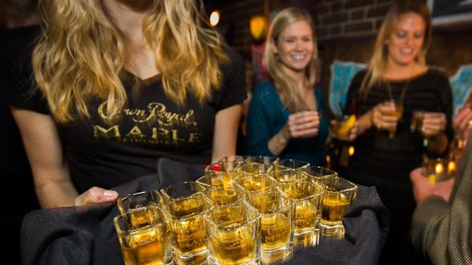 Shots of Crown Royal Maple are handed out during the Charleston Crown Royal Maple Finished Launch Party at Social Restaurant + Wine Bar Wednesday, January 30, 2013, in Charleston, S.C.  (Mic Smith / AP Images for Crown Royal)