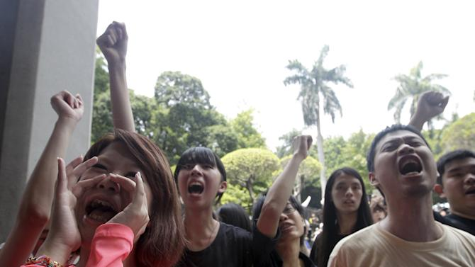 Students shout slogans during a protest at the entrance to the Ministry of Education in Taipei