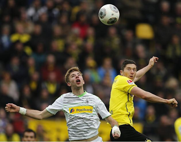 Moenchengladbach's Christoph Kramer, left, and Dortmund's Robert Lewandowski of Poland challenge for the ball during the German first division Bundesliga soccer match between BvB Borussia Dort