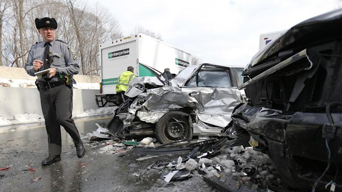 Pennsylvania State Police trooper inspects vehicles piled up in an accident, Friday, Feb. 14, 2014, in Bensalem, Pa. Traffic accidents involving multiple tractor trailers and dozens of cars have completely blocked one side of the Pennsylvania Turnpike outside Philadelphia and caused some injuries. (AP Photo/Matt Rourke)