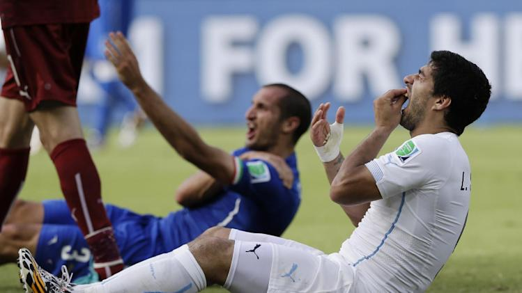 FILE - In this June 24, 2014 file photo, Uruguay's Luis Suarez holds his teeth after running into Italy's Giorgio Chiellini's shoulder during the group D World Cup soccer match between Italy and Uruguay at the Arena das Dunas in Natal, Brazil. Suarez was banned for nine competitive international matches, four months from all football and fined for biting Chiellini's shoulder during the group D World Cup soccer match. Football's international governing body on Thursday, July 10, 2014, said its appeals committee rejected Suarez's appeal against his ban for biting his opponent. (AP Photo/Ricardo Mazalan, File)