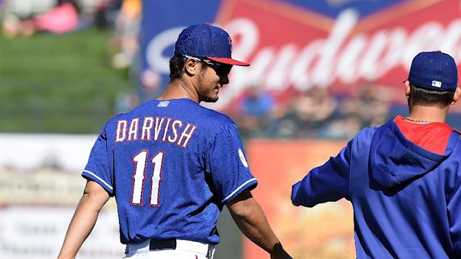Yu Darvish of the Texas Rangers talks to a teammate while walking back to the clubhouse after the fourth inning of a game against the Kansas City Royals on March 4, 2015 in Surprise, Arizona