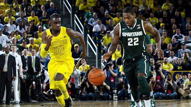 Michigan guard Tim Hardaway Jr., (10) and Michigan State guard Branden Dawson (22) chase after a loose ball in the first half of an NCAA college basketball game, Sunday, March 3, 2013, at Crisler Center in Ann Arbor, Mich. (AP Photo/Tony Ding)