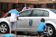 Workers wash a customer's car outside a restaurant in Beijing. China on Thursday cut interest rates for the first time in over three years and moved to allow rates to float more freely, in a bid to boost a slowing economy and advance financial reform