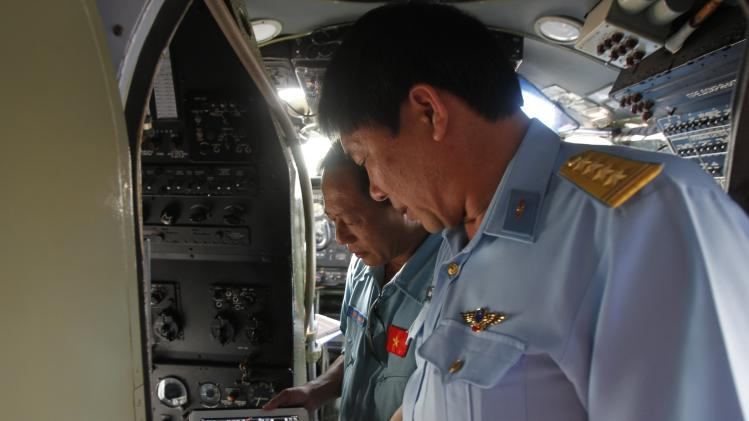 Senior Colonel Do Duc Minh talks with Captain Vu Duc Long before departing for their search and rescue mission for Malaysia Airlines flight MH370 at a military airport in Ho Chi Minh city
