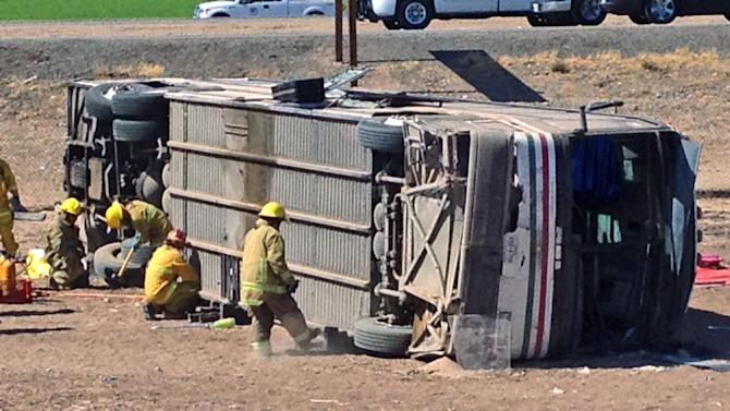 Emergency personnel respond to the scene of a fatal accident in Blythe, Calif. on Wednesday, May 21, 2014. A tractor-trailer spilled a load of steel pipes onto a highway, triggering a bus crash Wednesday that killed four people and seriously injured several others on the main road linking Southern California and Arizona, authorities said. (AP Photo/Brian Skoloff)