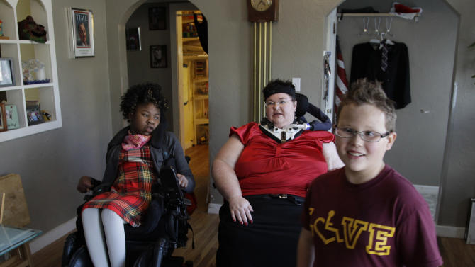 In this Nov. 14, 2012 photo, Carrie Ann Lucas, center, sits with her adopted daughter, Adrianne, 13, as her adopted son Anthony, 11, walks past them as he gets himself ready in the morning, at their home in Windsor, Colo. Carrie Ann Lucas uses a power wheelchair and is reliant on a ventilator due to a form of muscular dystrophy. She is a single mother of four adopted children, ages 22, 17, 13 and 11, all of whom also have disabilities, including two who use wheelchairs and three with intellectual disabilities. (AP Photo/Brennan Linsley)