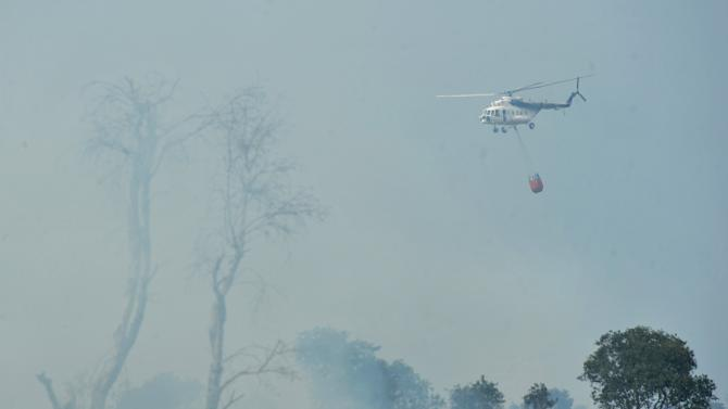 A helicopter belonging to Indonesia's National Disaster Management Agency carries water to be used to extinguish fire at the peatlands in Indralaya Ogan Ilir regency, South Sumatra