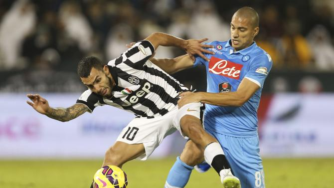 Juventus' Carlos Tevez  (L) fights for the ball with Napoli's Gokhan Inler during their Italian Super Cup soccer match  at Al-Sadd Stadium, in Doha