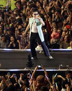 """FILE - South Korean rapper PSY, who sings the popular """"Gangnam Style,"""" performs during his concert in front of Seoul City Hall in Seoul, South Korea, in this, Oct. 4, 2012 file photo. YouTube says in a posting on its Trends blog that """"Gangnam Style"""" had been viewed 805 million times as of Saturday afternoon, Nov. 24, 2012 surpassing Justin Bieber's """"Baby,"""" which has had 803 million views to become YouTube's most viewed video of all time.. (AP Photo/Lee Jin-man, File)"""