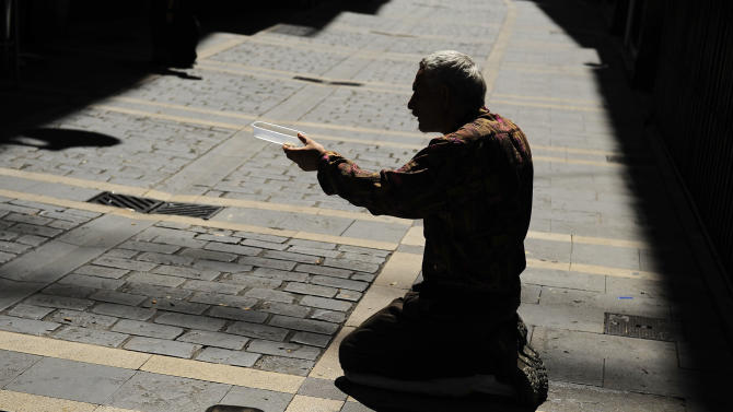 A man begs for alms as he sits in the hot sunshine on a lonely street in the old city of Pamplona, northern Spain, Thursday Aug. 23, 2012. (AP Photo/Alvaro Barrientos)