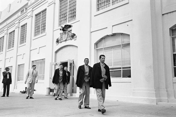In this March 21, 1963 photo taken by Leigh Wiener and provided by the National Park Service, prison guard Jim Albright, second from left, leads out the last prisoners from the federal penitentiary. The National Park Service on Thursday celebrated the 50th anniversary of Alcatraz Island's closure as a federal penitentiary with an exhibit of newly discovered photos of the prison's final hours. The new display opened five decades after the last shacked prisoners were taken off the infamous prison in San Francisco Bay that once held the likes of gangsters Al Capone and Mickey Cohen. (AP Photo/National Park Service, Copyright Leigh Wiener)