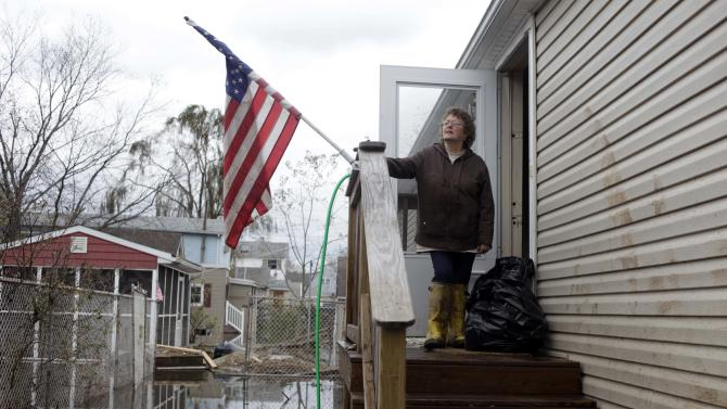 Eileen Miley takes a break from cleaning her home that was destroyed by flooding during Storm Sandy in Staten Island, New York, Thursday, Nov. 1, 2012. Three days after Sandy slammed the mid-Atlantic and the Northeast, New York and New Jersey struggled to get back on their feet, the U.S. death toll climbed to more than 80, and more than 4.6 million homes and businesses were still without power. (AP Photo/Seth Wenig)