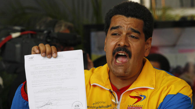 Venezuela's acting President Nicolas Maduro shows his certificate after registering his presidential candidacy to replace late President Hugo Chavez at the national electoral council in Caracas, Venezuela, Monday, March 11, 2013. Presidential elections were announced to take place on April 14, after the death of Chavez on March 5. (AP Photo/Ariana Cubillos)
