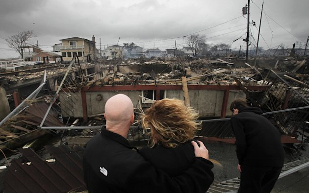 "FILE - In this Tuesday, Oct. 30, 2012, file photo, Robert Connolly, left, embraces his wife Laura as they survey the remains of the home owned by her parents that burned to the ground in the Breezy Point section of New York, during Superstorm Sandy. The current term of the U.S. Congress is set to end this week with no action on aid for the superstorm that left more than 100 dead and thousands homeless in three northeast states. Governors Andrew Cuomo of New York and Chris Christie of New Jersey said in a joint statement Wednesday, Jan. 2, 2013 that the ""continued inaction and indifference"" by the House ""'is inexcusable."" (AP Photo/Mark Lennihan, File)"