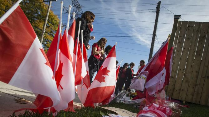 Workers from the St. Eugene Catholic Elementary School, where Cpl. Nathan Cirillo's son is enrolled, pay respects at a makeshift memorial in honour of Cpl. Cirillo, outside the family home in Hamilton