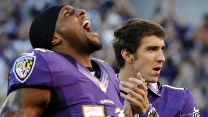 Baltimore Ravens linebacker Ray Lewis, left, and Olympic swimmer Michael Phelps react as members of the Ravens take the field before an NFL football game against the Cincinnati Bengals in Baltimore, Monday, Sept. 10, 2012. (AP Photo/Patrick Semansky)