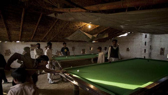 Pakistani men play billiards in a makeshift club in Islamabad's slums Friday, Nov. 28,  2014, in Pakistan. The club owner hopes to renovate the roof before the monsoon season. (AP Photo/B.K. Bangash)