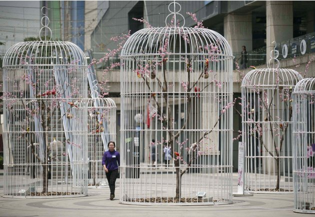 A woman walks past an installation of giant bird cages installations on a square in Nanjing