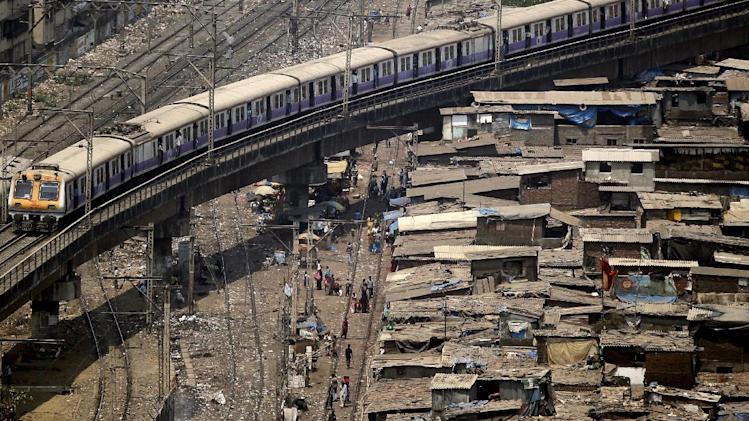 A local train moves on an elevated track over a slum area in Mumbai, India, Thursday , March 15, 2012. Indian Railways Minister Dinesh Trivedi announced the first railway fare hike in eight years Wednesday, only to be shot down moments later by Congress party leader Mamata Banerjee, a populist politician who said she would not allow any fare hike in the 600 billion rupee ($12 billion) rail budget. (AP Photo/ Rajanish Kakade)