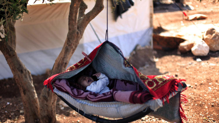 A Syrian baby cries as he lays on a swing attached to a tree at a displaced camp, in the Syrian village of Atma, near the Turkish border with Syria, Monday, Nov. 5, 2012. (AP Photo/ Khalil Hamra)