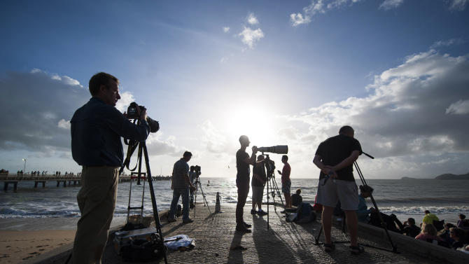 In this photo released by Tourism Queensland, people gather on a beach at Palm Cove in Queensland state, Australia, to watch and photograph a total solar eclipse Wednesday, Nov. 14, 2012. Starting just after dawn, the eclipse cast its 150-kilometer (95-mile) shadow in Australia's Northern Territory, crossed the northeast tip of the country and was swooping east across the South Pacific, where no islands are in its direct path. (AP Photo/Tourism Queensland, Murray Anderson-Clemence) EDITORIAL USE ONLY