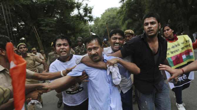 FILE – In this Sunday, Aug. 26, 2012 file photo, Indian anti-corruption activist Arvind Kejriwal, center, is shielded by supporters as he flees police during clashes at a protest near the Prime Minister's official residence in New Delhi, India. Launching his own political party this month, longtime bureaucrat-turned-activist Kejriwal taps into the disgust of ordinary Indians amid a seemingly unending stream of corruption scandals that have tainted politicians of all stripes over the last few years. (AP Photo/Kevin Frayer, File)