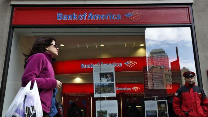 File photo of a woman walking past as customers use ATMs at a Bank of America banking center in New York's financial district