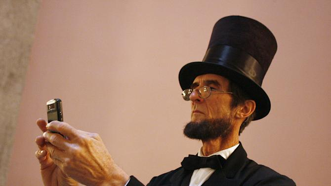 Robert Broski, a member of the Association of Lincoln Presenters, takes a photo with his cell phone during a visit to the Ohio Statehouse on Friday, April 12, 2013 in Columbus, Ohio. The three dozen presenters were there to hear a Lincoln speech in the House chamber given by fellow presenter Jerry Payn.  About three dozen Abraham Lincoln impersonators from around the U.S. are convening in Columbus for their 19th annual convention to compare notes and costumes and tour some Abe-related historical sites. (AP Photo/Mike Munden)