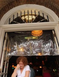 Adrienne Lamb reads in a window in the French Quarter beneath plastic tarp in preparation for Hurricane Isaac in New Orleans, Louisiana