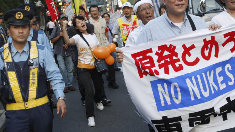 Demonstrators walk by the headquarters of Tokyo Electric Power Co., the operator of tsunami-hit Fukushima Dai-ichi nuclear plant, during their anti-nuclear power protest in Tokyo Thursday, June 30, 2011. Japanese reads: Stop nuclear power plants. (AP Photo/Shizuo Kambayashi)