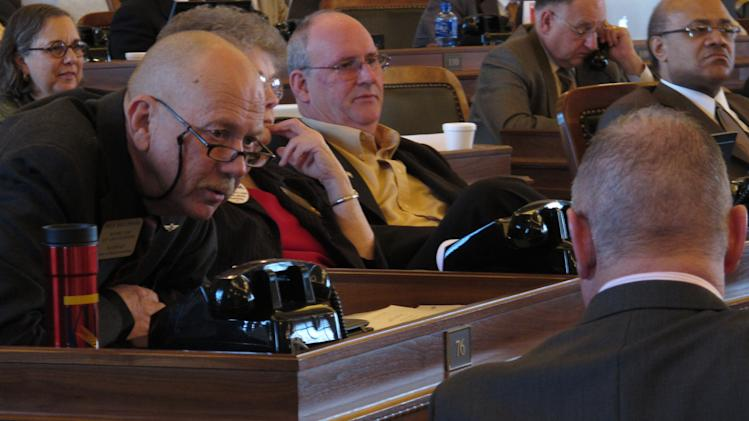 State Rep. Nile Dillmore, left, a Wichita Democrat, confers with Rep. Doug Gatewood, right, with his back to the camera, a Columbus Democrat, during a Kansas House vote on a bill cutting income and sales taxes, Wednesday, March 14, 2012, at the Statehouse in Topeka, Kan. Dillmore opposes the measure, arguing the bill will create an ongoing budget crisis. (AP Photo/John Hanna)