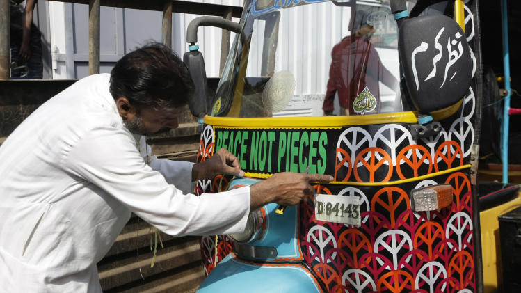 In this Saturday, Feb. 2, 2013 photo, Pakistani artist Nusrat Iqbal puts final touches to a rickshaw in Karachi, Pakistan. Pakistani youth leader Syed Ali Abbas Zaidi has an innovative plan to counter the relentless message of violence spewed forth by radical Islamic groups in the country and is stealing a trick from their playbook to do it. His weapon: the three-wheeled motorized rickshaws that buzz along Pakistan's streets carrying paying customers. (AP Photo/Fareed Khan)