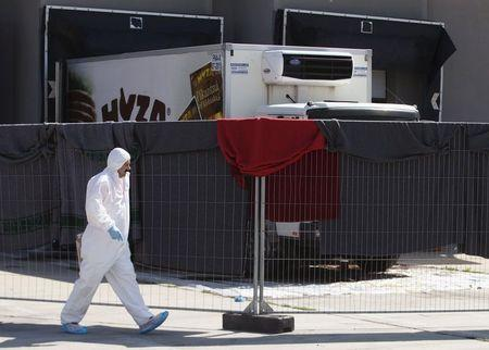 A member of a forensic team walks in front of a truck in which more than 70 bodies were found, at a customs building with refrigeration facilities in the village of Nickelsdorf