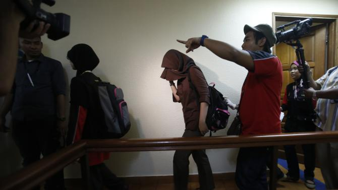 Malaysian Islamic religious officers detain a Muslim woman after she was found together in the same room with a man at a budget hotel during a raid in Kuala Lumpur