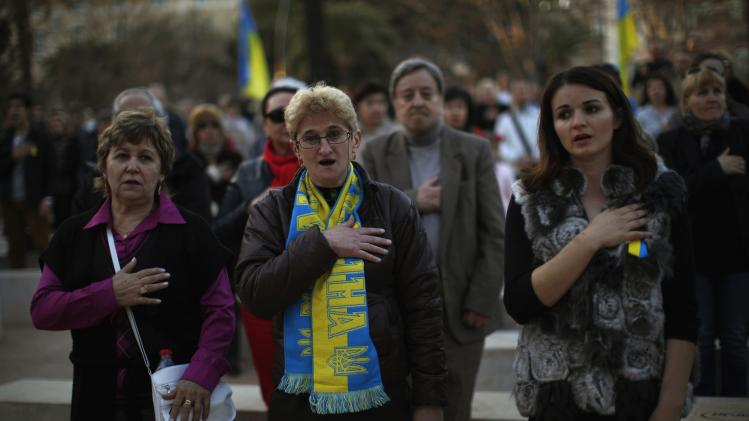 Ukrainians living in Malaga sing the Ukrainian anthem during a protest against Russian President Vladimir Putin and in favor of unity and democratic freedom in Ukraine, in downtown Malaga