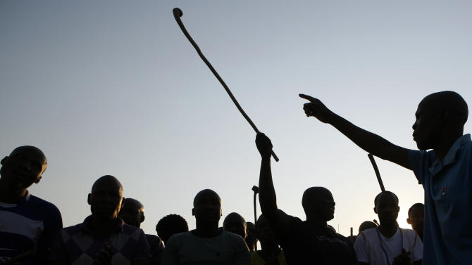 An unidentified mine workers sing a dance during their meeting at the Lonmin Platinum Mine near Rustenburg, South Africa, Wednesday, Aug. 29, 2012. Two weeks ago 34 miners were shot and killed by police and more than 200 miners have appeared in court facing violent strike related incidents. (AP Photo/Themba Hadebe)