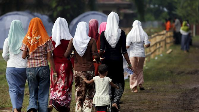 Rohingya migrants who arrived in Indonesia last week by boat walk back after collecting breakfast at a temporary shelter in Aceh Timur regency near Langsa in Indonesia's Aceh Province