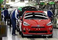 File photo shows workers making final checks on Toyota&#39;s compact hybrid vehicle AQUA on its assembly line in Tokyo. Japan logged a bigger-than-expected trade deficit of $6.5 bn in April as higher energy costs pushed up imports, the finance ministry said Wednesday