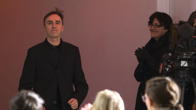 Belgian fashion designer Raf Simons appears at the end of his Men's Spring-Summer 2013 collection, during Paris Fashion Week, in Paris, France, Wednesday, Jan. 16 2013. (AP Photo/ Jacques Brinon)