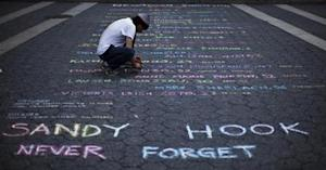 Street artist Panzarino prepares a memorial as he writes the names of the Sandy Hook Elementary School victims during the six-month anniversary of the massacre, at Union Square in New York