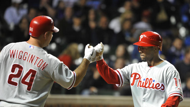 Philadelphia Phillies' Ty Wigginton, left, high-fives teammate Jimmy Rollins after Rollins and Roy Halladay scored on a throwing error by Chicago Cubs relief pitcher Blake Parker during the eighth inning of a baseball gameon Thursday, May 17, 2012 in Chicago. (AP Photo/Brian Kersey)