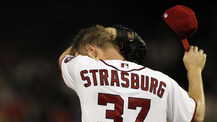 Washington Nationals starting pitcher Stephen Strasburg wipes his face on the mound during the second inning of a baseball game against the Miami Marlins at Nationals Park, Friday, Sept. 7, 2012, in Washington. (AP Photo/Alex Brandon)