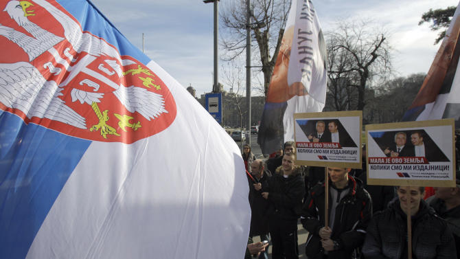 A protester waves a Serbian flag during the protest in front of the presidency building in Belgrade, Serbia, Tuesday, Feb. 5, 2013. Dozens of ultranationalists have accused Serbia's president of treason for agreeing to meet with his counterpart from Kosovo for the first time since the end of the war in 1999. The talks between Tomislav Nikolic and Atifete Jahjaga on Wednesday in Brussels, Belgium, will be part of an EU-brokered effort to improve ties between the former foes. (AP Photo/Darko Vojinovic)