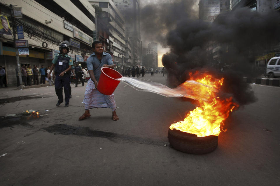Riot police watch as a shopkeeper throws water to control fire after Bangladesh Nationalist Party or BNP activists set the fire to drum up support for their nationwide strike in Dhaka, Bangladesh, Wednesday, Sept. 21, 2011. Bangladesh Nationalist Party and their alliance call nationwide strike to protest against fuel price hike. (AP Photo/ Pavel Rahman)