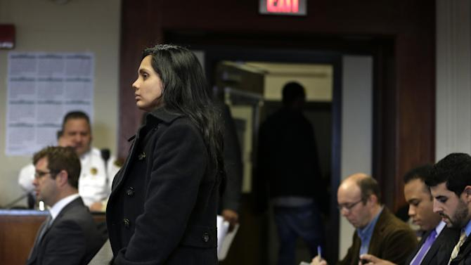 Annie Dookhan, front left, stands during her arraignment at Suffolk Superior Court, in Boston, Thursday, Dec. 20, 2012. Dookhan, the former chemist at the center of a U.S. drug testing scandal, pleaded not guilty to charges including perjury and tampering with evidence. (AP Photo/Steven Senne, Pool)